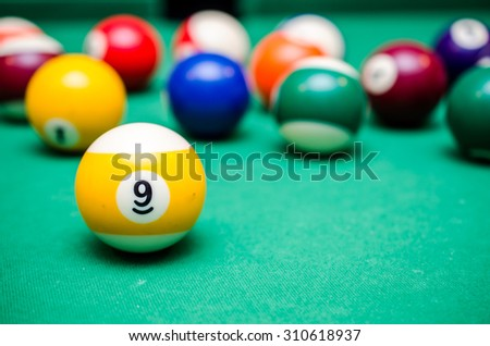 9 Ball from pool or billiards on a billiard table - stock photo