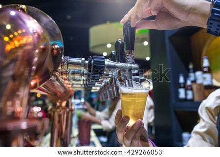 Barman brewing a beer tap pouring a draft beer  - stock photo