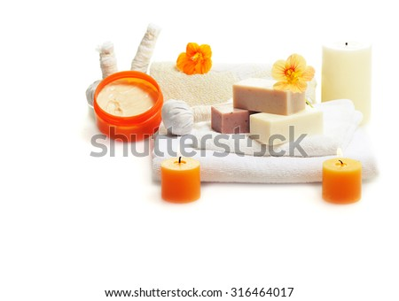 bars of herbal spa soap with white towels,candles and flower - stock photo