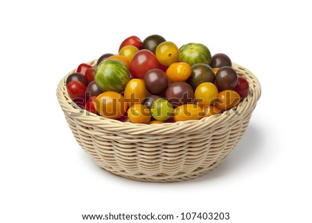 Basket with different color homegrown organic tomatoes on white background - stock photo