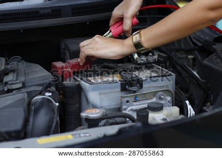 Battery charging cables connect to a car battery - stock photo