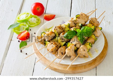 BBQ chicken kebabs with zucchini on a white wooden background - stock photo