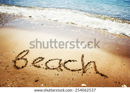 """Beach"" written in the sand on sea background - stock photo"
