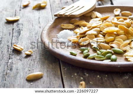 Beans roasted snack and salt on wood plate - stock photo