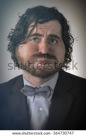 Bearded man holds his breath in anticipation and is turning blue - stock photo