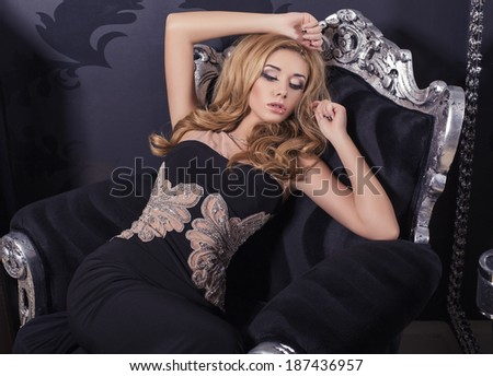 beautiful blond woman in elegant black dress sitting on armchair - stock photo