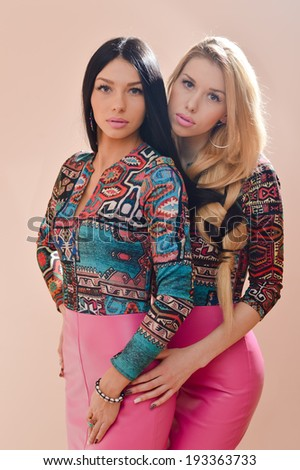 2 beautiful blonde and brunette sexy young women girl friends or sisters having fun standing together in pink leather dresses looking at camera on ivory background portrait - stock photo