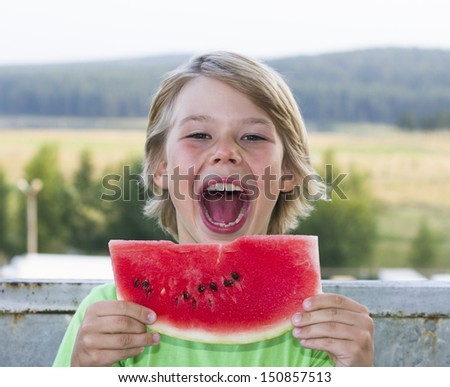 Beautiful boy eats a piece of watermelon outdoors - stock photo