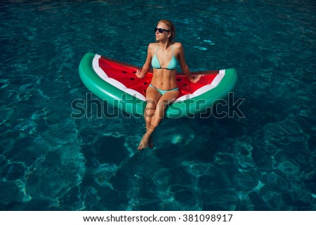 Beautiful exotic woman with  inflatable watermelon tanning  in pool. Woman in swimming  pool. - stock photo