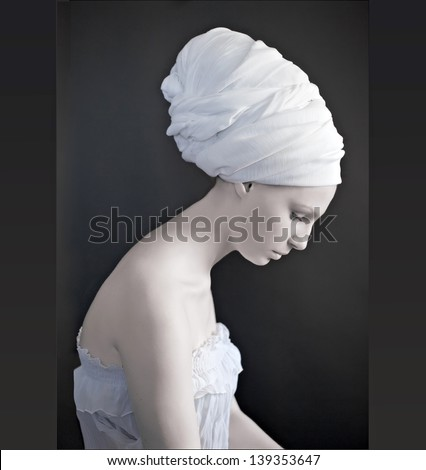 beautiful female model looking as marble statue, wearing head wrap - stock photo