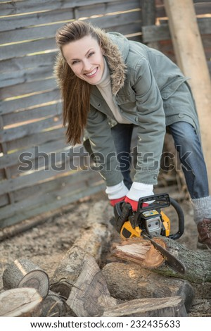 Beautiful female woodworker with chainsaw. focus on face - stock photo