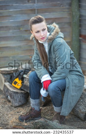Beautiful female woodworker with chainsaw in the evening - stock photo