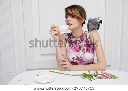 Beautiful Girl Drinking Tea or Coffee in Cafe.  With african grey parrot on shoulder, rose lupin flower on white table.  - stock photo