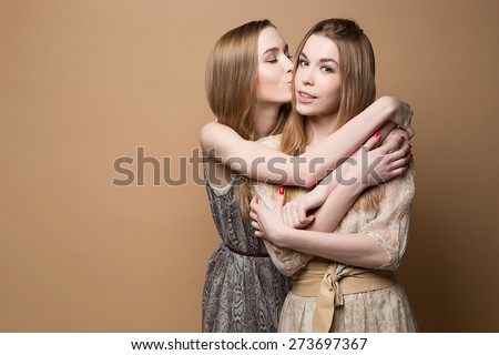 2 beautiful girls twins in the studio. fashion, seduction. Two beautiful sexy tanned girls with long hair - stock photo