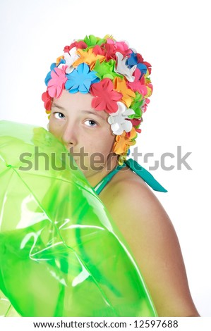 Beautiful little girls in a flowered swim cap blowing up a bright green inner-tube - stock photo