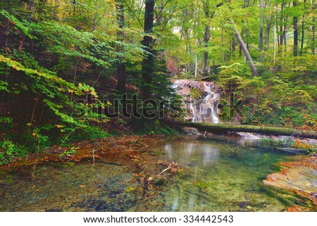 beautiful pond in the woods, Ochiul Beiului, Caras Severin county, Romania, water fall in the autumn forest  - stock photo
