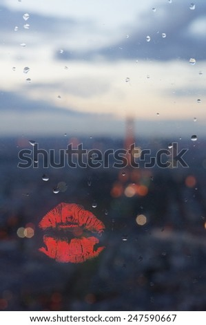 Beautiful red lips isolated on window from Montparnasse Tower at night. soft evening light, focus on lips - stock photo