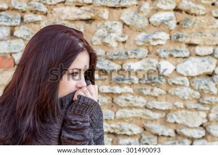 beautiful sad young woman on a stone wall background - stock photo
