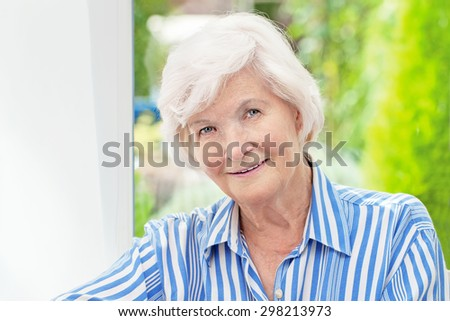 Beautiful senior woman sitting in her winter garden , in the background the garden - stock photo
