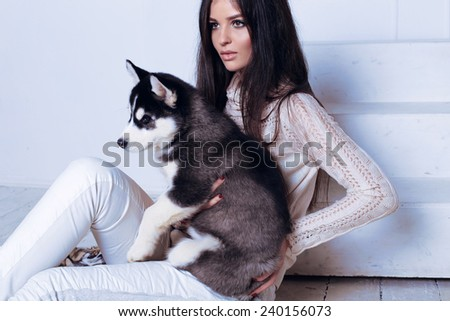 beautiful sexy brunette women with long straight hair wearing sweater,trousers and necklace relaxing at home,sitting on the wood floor near staircase,and holding a cute little puppies of Husky - stock photo