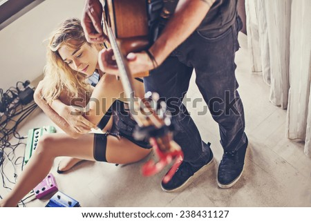 beautiful sexy girl and her boyfriend playing guitar  - stock photo