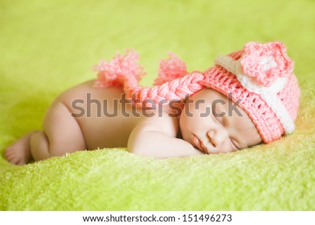 beautiful sleeping baby  wearing a striped hat - stock photo