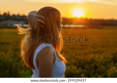 beautiful slender red-haired girl looks at the sunset - stock photo