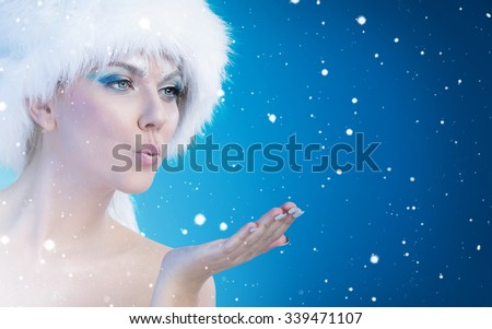 Beautiful snow queen blowing in her open palm - stock photo