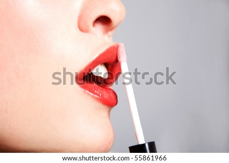 beautiful woman applying lipstick,studio shoot - stock photo
