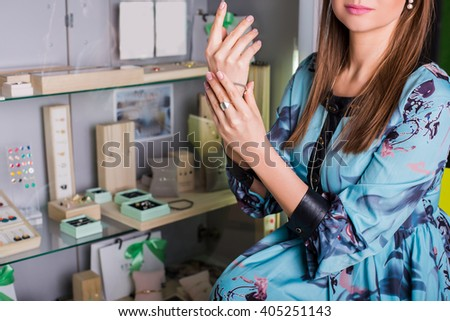 beautiful woman buyer, chooses jewelry. In the background showcase with jewelry.Concept of  luxurious and wealth  life - stock photo