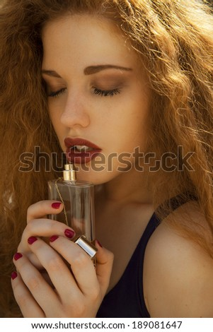 beautiful woman holding bottle of perfume and smelling aroma. vertical shot, studio. - stock photo