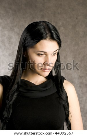 Beautiful woman in a black dress with long hair - stock photo
