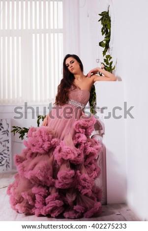beautiful woman in a dress wonderful, studio interyerniy. Full length portrait. Fashion photography. - stock photo