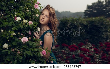Beautiful woman in rose garden - stock photo