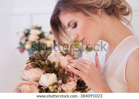 beautiful woman model with fresh daily makeup and romantic wavy hairstyle, holding a bouquet of flowers - stock photo