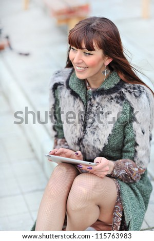 Beautiful woman using tablet in the park - stock photo