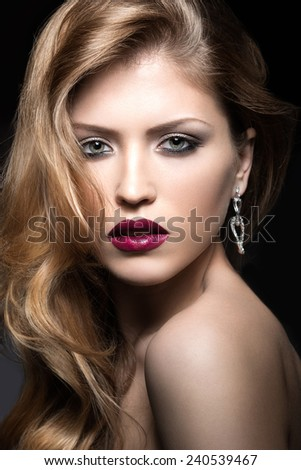Beautiful woman with evening make-up, red lips and curls. Beauty face. Picture taken in the studio on a gray background. - stock photo