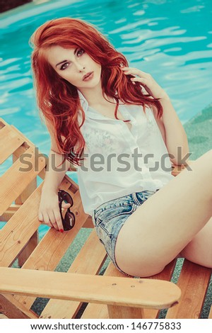 beautiful young girl with red hair lying on a sunbed near the swimming pool - stock photo