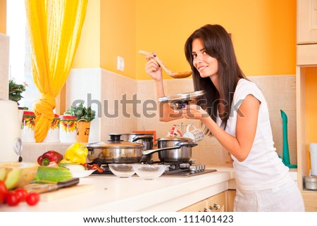 Beautiful young housewife in the kitchen - stock photo