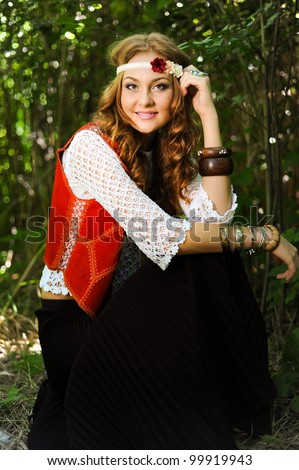 Beautiful young woman hippie sitting outdoor - stock photo