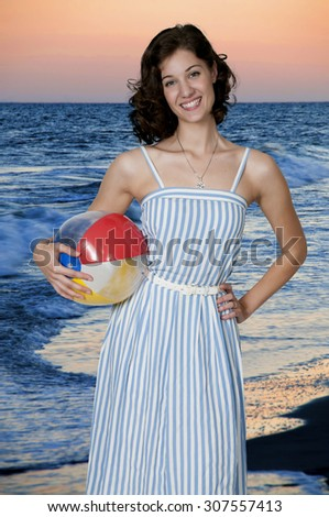 Beautiful young woman holding a beach ball - stock photo