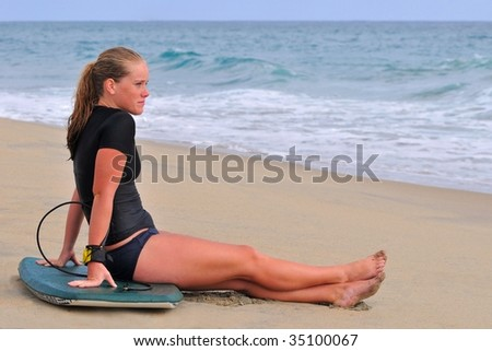 Beautiful young woman watches waves with bodyboard on beach - stock photo