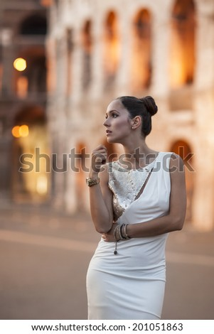Beauty woman at night with coloseum in background - stock photo