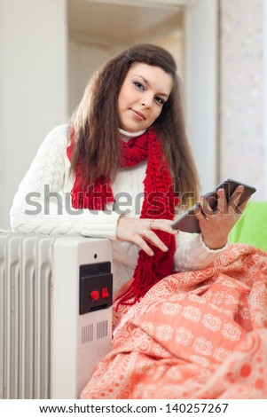 beauty woman reads e-book near oil heater in home - stock photo