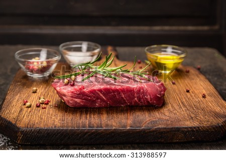 Beef steak with ingredients for cooking - rosemary,oil, and spices on rustic cutting board over dark wooden background. - stock photo
