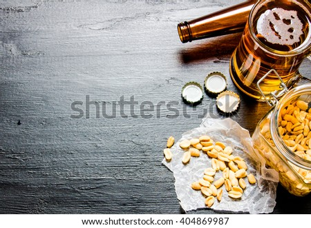 Beer with peanuts on the black wooden table. Free space for text. - stock photo