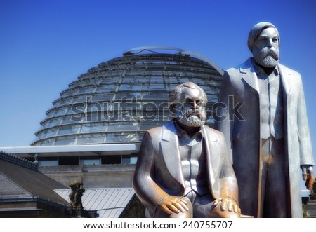 BERLIN, GERMANY - JULY 25, 2012: the Monument of Marx and Engels in the city center Berlin, the Reichstag in the background - stock photo