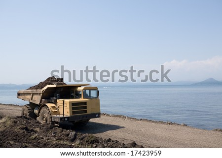 Big dump truck.Construction of new seaport. - stock photo