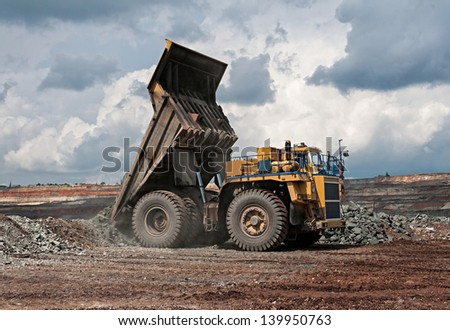 big yellow mining truck unload iron ore - stock photo