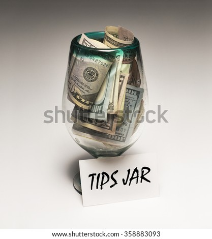 $50 bills and $100 bills in tips jar with sign - stock photo